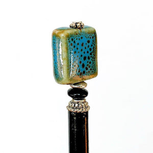 A side view of the Lark Tidal Hair Stick made from square blue raku fired ceramic beads.