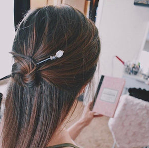 A brunette millennial woman wears a topknot using the Luna Tidal Hair Stick made from Rainbow Moonstone nugget beads.