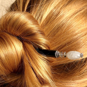 A blonde messy bun is held up by the Luna Tidal Hair Stick made from Rainbow Moonstone nugget beads.