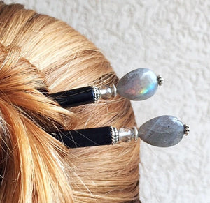 A woman wears two of the Malia Tidal Hair Sticks made from gray Labradorite stone beads.