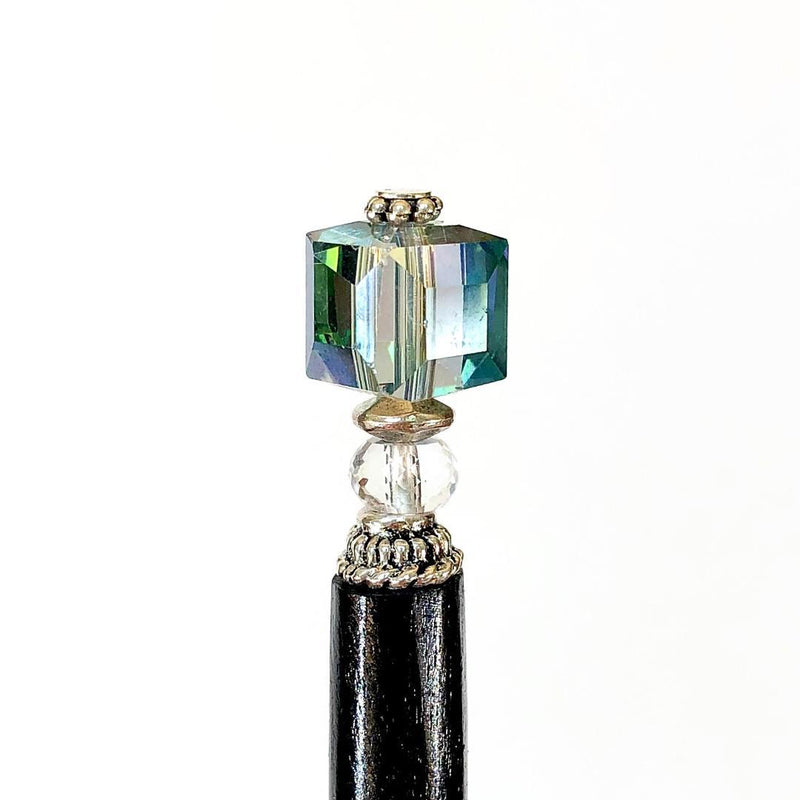 A close up of the Marley Tidal Hair Stick made from iridescent blue glass beads.