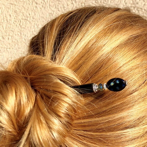 A blonde woman wearing a hair bun with the Melanie Tidal Hair Stick made from black Czech glass beads.