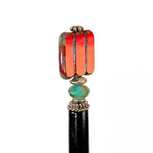 A side view of the Nela Tidal Hair Stick made from a red Czech glass bead.