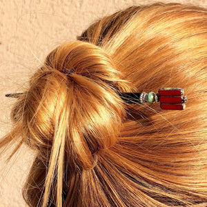 A blonde woman wears a messy bun using the Nela Tidal Hair Stick made from a red Czech glass bead.