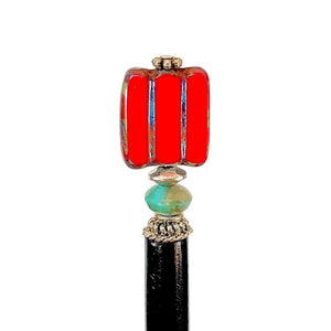 A close up of the Nela Tidal Hair Stick made from a red Czech glass bead.