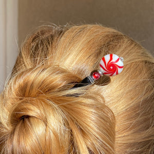 A woman wearing on of our Noelle Hair Stick made from a glass bead that looks like peppermint candy.