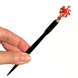 A full picture of our Noelle Hair Stick made from a glass bead that looks like peppermint candy.