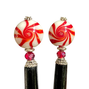 A close up of two of our Noelle Hair Sticks made from glass beads that looks like peppermint candy.