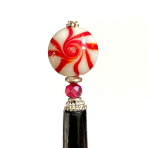 A close up of our Noelle Hair Stick made from a glass bead that looks like peppermint candy.