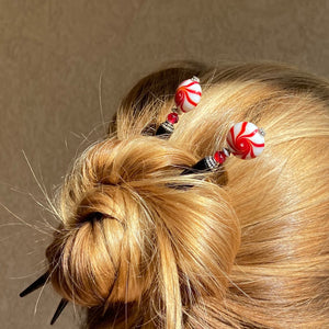 A woman wears two of our Noelle Hair Stick made from a glass bead that looks like peppermint candy.