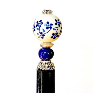 A close up of the Nora Tidal Hair Stick made from blue flowered white ceramic beads.