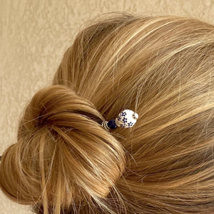 A woman wears a Nora Hair Stick in her hair bun.