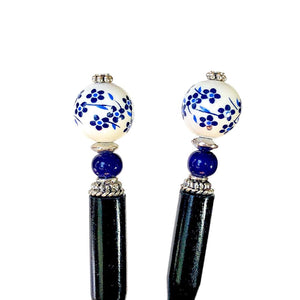 Two of the Nora Tidal Hair Sticks made from blue flowered white ceramic beads.