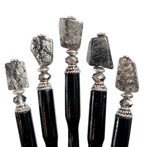A close up of 5 of our Palmer Hair Sticks made from black rutile quartz stone.