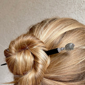 A woman wearing a hair bun using one of our Palmer Hair Sticks made from black rutile quartz stone.
