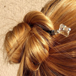 A blonde woman wears a messy bun with the Penelope Tidal Hair Stick made from iridescent clear glass beads.