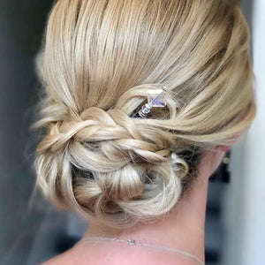 A blonde woman wears a bridal hairstyle using the Penelope Tidal Hair Stick made from iridescent clear glass beads.