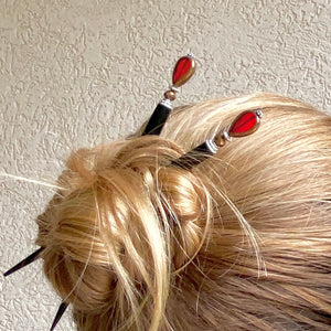 A woman wearing a hair bun using two of our Reina Hair Stick made from a red Czech glass bead with bronze edging.