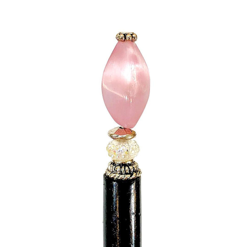A close up of the Roxy Tidal Hair Stick made of pink cat's eye glass.
