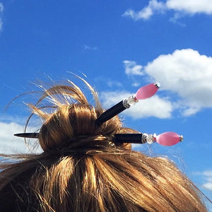 A woman wears a high bun with two of the Roxy Tidal Hair Sticks made of pink cat's eye glass.