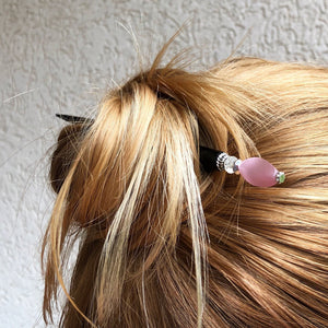 A woman wearing a messy bun with the Roxy Tidal Hair Stick made of pink cat's eye glass.
