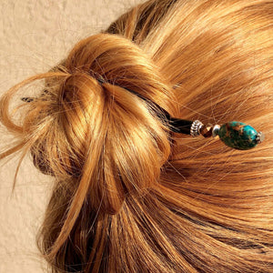 A woman wears a messy bun using the Terra Tidal Hair Stick made from blue Jasper stone beads.