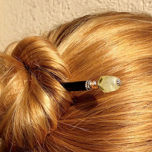 A blonde woman wears a messy hair bun using the Vera Tidal Hair Stick made of yellow green Prehnite Stone beads.