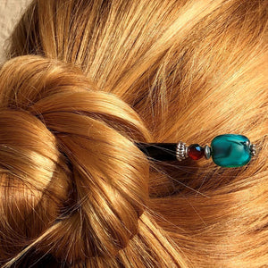A woman wears her hair in a bun using the Zara Hair Stick made from teal blue and red swirl Czech glass beads.