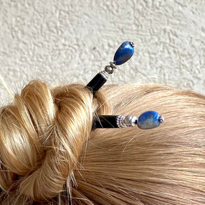 A woman wears two of our Chloe Tidal hair Sticks made from Lapis Lazuli Nuggets