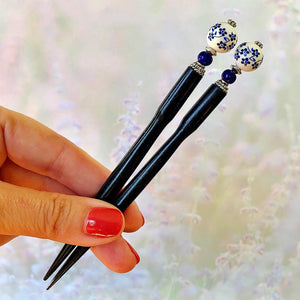 A hand holding two of the Nora Tidal Hair Sticks made from blue flowered white ceramic beads.