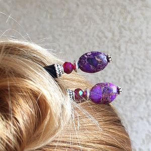 A woman wears a hair bun with two of the Petra Tidal Hair Sticks made with purple jasper stone beads.