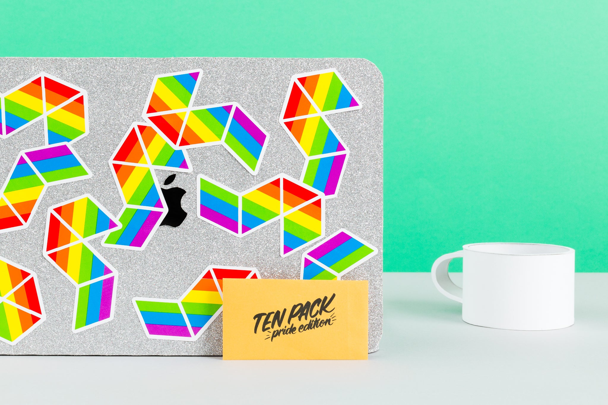10 rainbow pride stickers, shown on desk with laptop