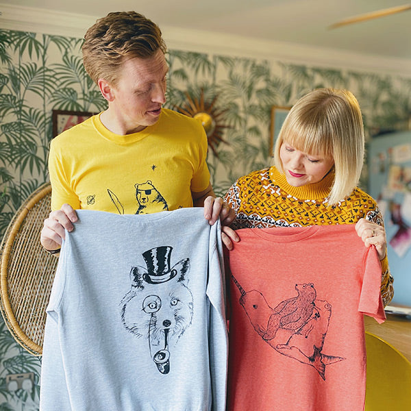 lucy and tom holding up t-shirts