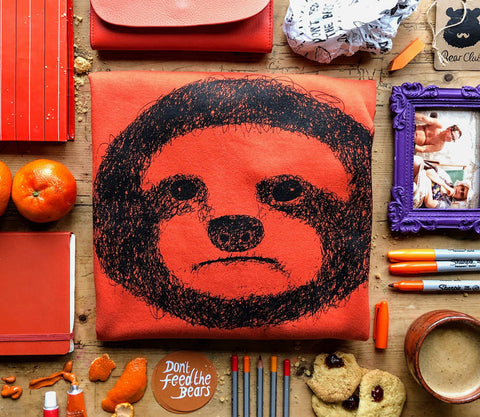 sloth orange jumper flat lay