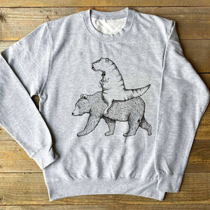 a t-rex riding bear on a grey jumper