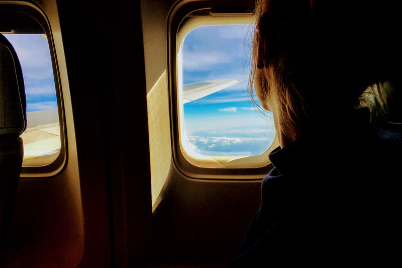 Girl looking outside an airplane window