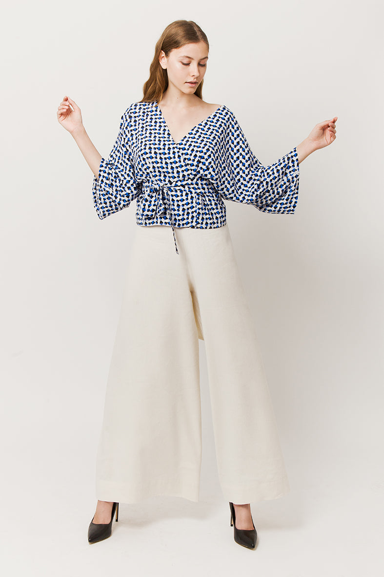 Model in tiche total look - blue wrapover kimono top and white pants