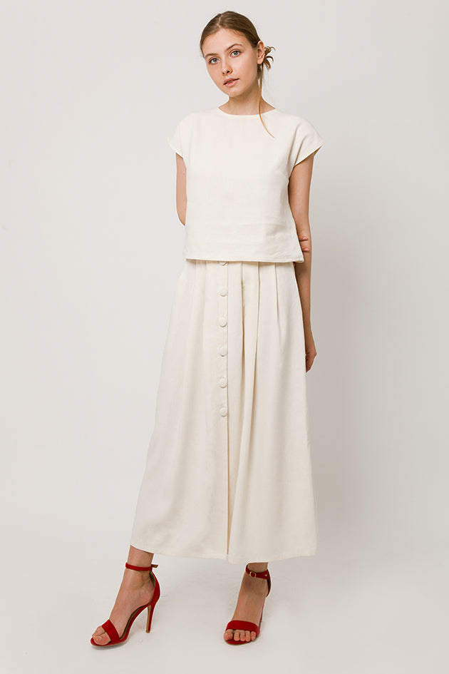 Model in linen-silk sleeveless white top and white skirt with bottons