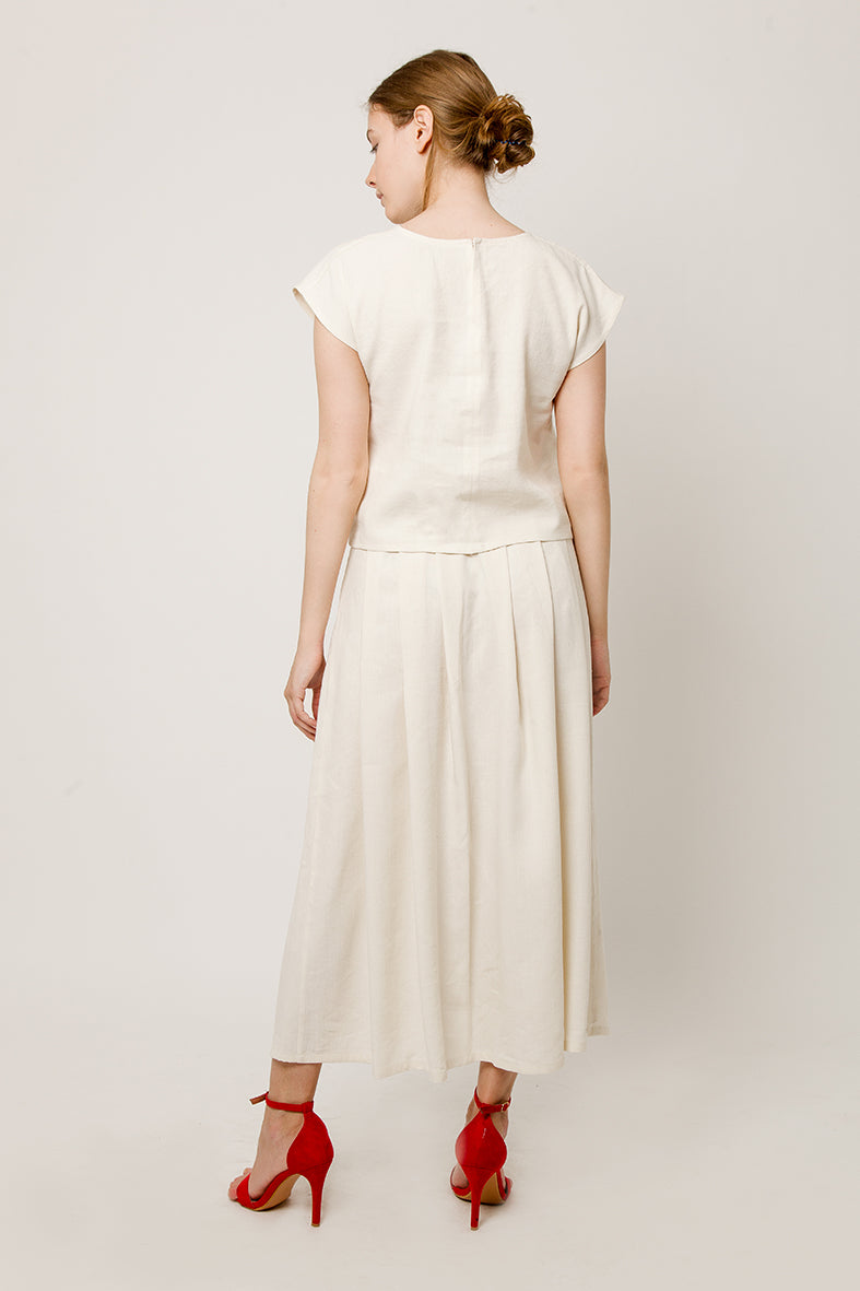 Model in total tiche look - linen-silk sleeveless white top and dress - back view
