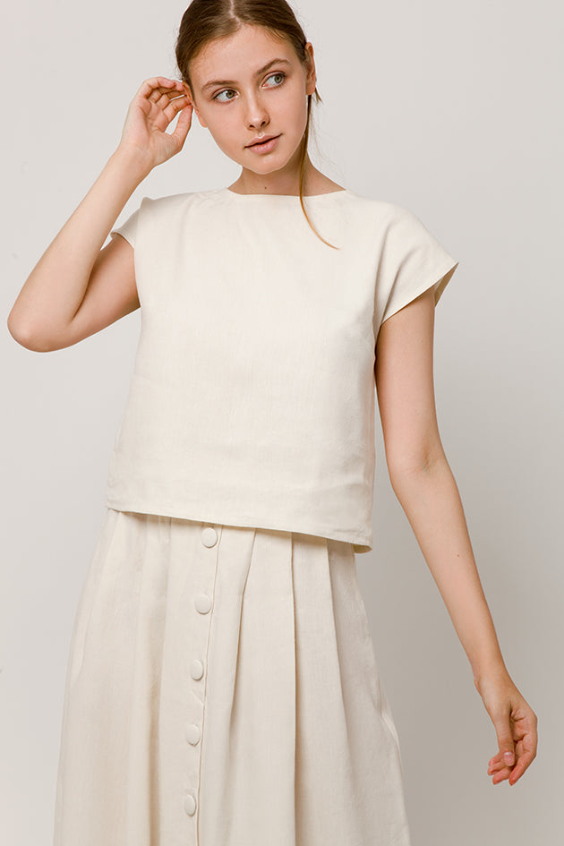Model in linen-silk sleeveless white top and front button dress