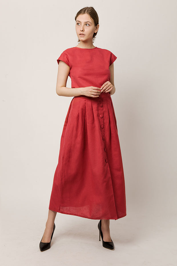 Model in cap-sleeve top in a deep-red color and long skirt