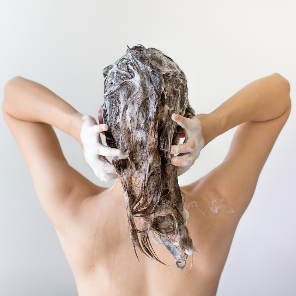 Woman in shower using shampoo and conditioner bars which are all natural and available now Boutique Love Attack