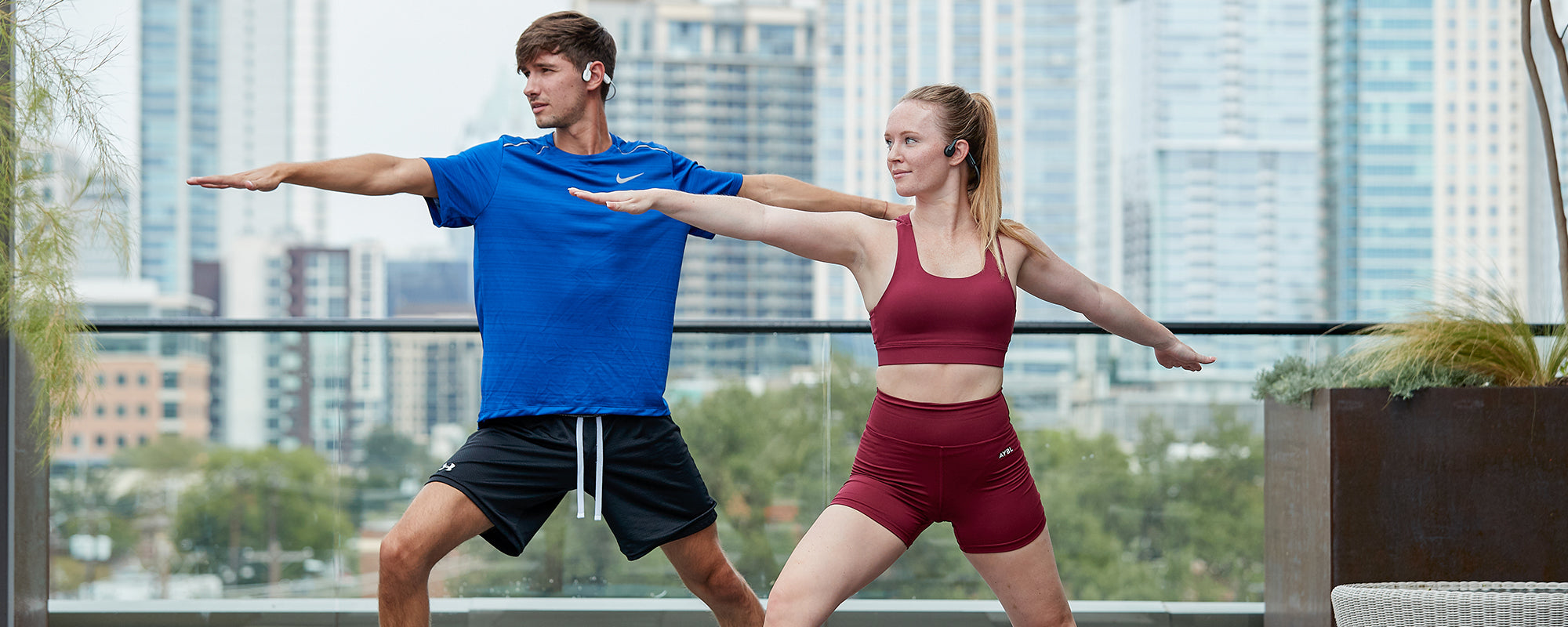 Man and woman doing yoga while wearing AfterShokz OpenMove headphones