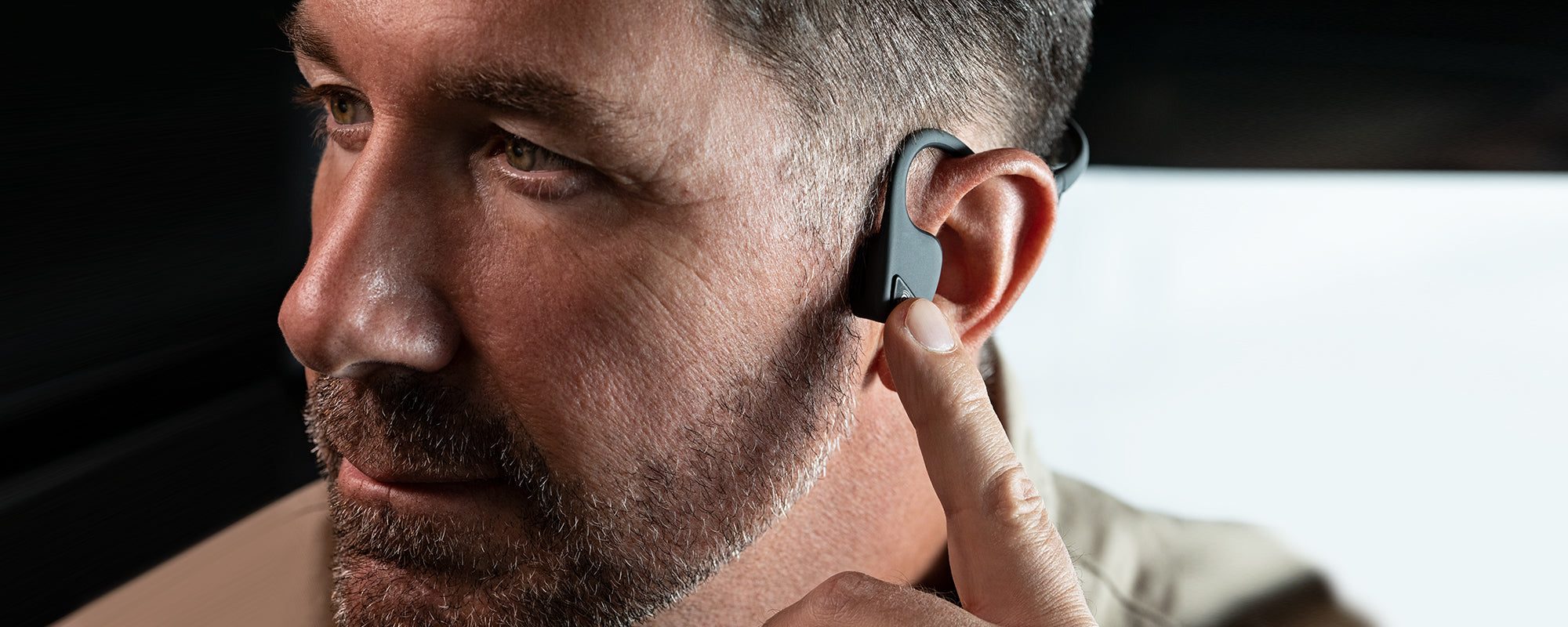 Man wearing AfterShokz Aie endurance-lifestyle wireless headphones