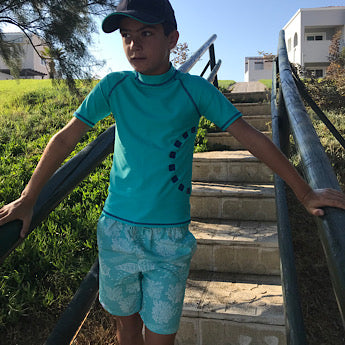 Turquoise turtle print board shorts
