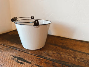 "Vintage white enamel pail with blue rim and wood handle. No leaks! This is a smaller unique size and measures 7"" tall x 9"" wide at the top. Home decor and styling services by At the Farmhouse."