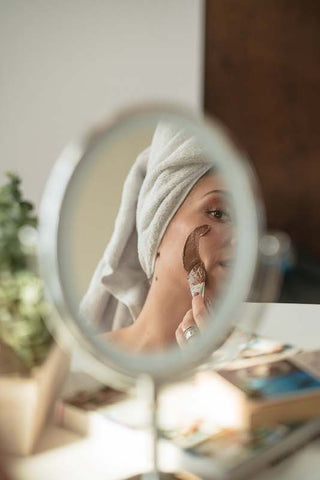 Applying Clay Face Mask on skin in mirror