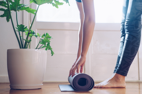Yoga mat unrolled with hands and feet on floor