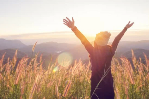 young woman with arms in air outside in nature
