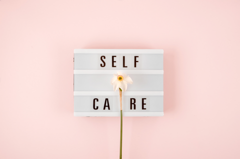 self care signage with flower and pink background